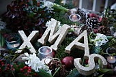 Christmas arrangement of fir branches, wintergreen, bay, apples, mistletoe, hyacinths, pine cones, tealights and the word XMAS