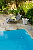 Wooden rocker lounger and potted palm on terrace next to pool