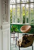Zwei bequeme Stühle und Tisch in klassischem Wintergarten mit grünen Wandfliesen und Mosaikboden