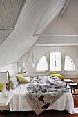 Noch ungemachtes Doppelbett in charmantem Dachzimmer mit unterteiltem Rundbogenfenster und weisser Holzverschalung