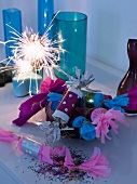 New Year's Eve party - party poppers and lit sparkler in front of coloured glass vases on sideboard