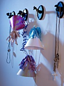 Decorative party hats and necklaces hanging from animal-shaped wall hooks
