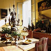 Rustic dining area with magnificent candelabra and fruit and wine bottles on sideboard; still-life paintings and stuffed pheasant on walls