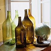 Old, empty bottles lit from behind, silver jug and ceramic sphere on cabinet
