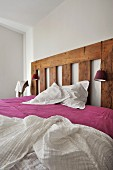 Bed with rustic wooden headboard and white throw over purple bedspread in minimalist bedroom