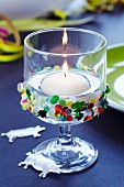 Floating candle in glass decorated with confetti & lucky pig charms