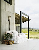 Terrace of a home located in an open landscape with an inviting sofa and crate table in front of an exposed concrete wall