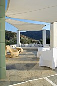 Awnings stretched between columns on Mediterranean terrace with comfortable seating