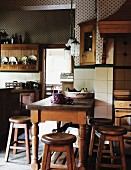 Rustic wooden table and stool in a country kitchen with white wall tiles
