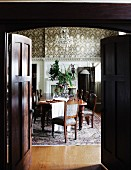 View through a dark wooden double door into a traditional dining room with a long dining table and colonial style, antique chairs
