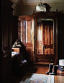 Colonial style, antique armoire with mirror and boots on wood flooring in the corner of a country bedroom