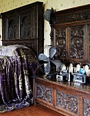 Antique fan and cameras on a carved wooden bench with high back next to a bed with a dark wood headboard and shimmering, violet bed coverlet
