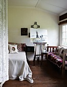 Easel with picture between a bed and bench by the window, at the side a lace curtain partially obscured from view in a no frills bedroom