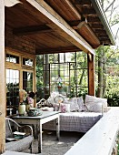 Cozy corner of a country home veranda with day bed and pillows in front of a stained glass wall and a view of trees