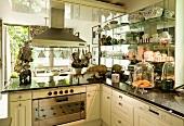 Moderne Küche im Landhausstil mit Dunstabzug und Geschirrsammlung auf seitlichen Glasregalen; kleine, freundliche Keramikschweine auf der Marmorarbeitsfläche