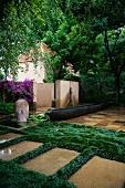 Künstlerisch angelegter Garten mit Objekten und Grasflächen neben gefliesten Flächen