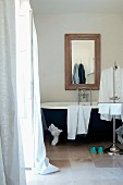 Towels and man's shirts on valet stand in front of vintage clawfoot bathtub below framed mirror on wall in modern interior