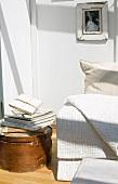 White blanket on sofa next to stack of books on round vintage storage box on floor