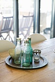 Vintage swing-top bottles on tray and rustic wooden table in front of terrace window