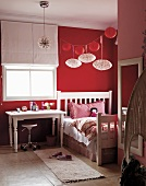 Red and white girl's bedroom - red and white lanterns above vintage bed next to desk below window with half-open blind