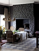 Dining table in front of dark stone chimney breast on vintage-style chequered floor