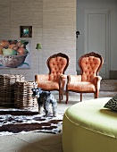 Neo-rococo armchairs with red upholstery next to wicker stools on cow-skin rug in modern living room