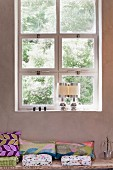 Cushions on bench below window with square casements and pair of postmodern table lamps on sill