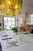 Designer chandelier above table set with floral plates and lace placemats in classic loft interior with industrial windows and exposed concrete