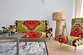Sofa and chair upholstered in eye popping Kilim, wicker floor lamp; table and rug in shades of gray