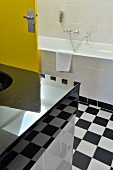 Modern bathroom with a retro touch, vanity with high gloss counter top (partially obscured from view) and yellow door with a black and white checkerboard pattern floor
