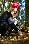 Woman gathering autumn leaves in woods