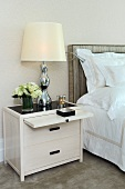 Bedside table with extendable surface and table lamp next to bed with upholstered headboard