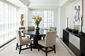 Round, dark wood table and upholstered chairs in dining room with floor-to-ceiling windows and half-closed blinds