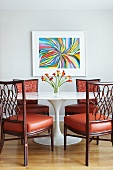 Classic table with marble top and wooden chairs with red leather seat cushions in front of modern artwork on wall