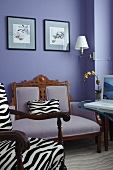 Armchair with zebra-pattern upholstery in front of antique armchair against lilac wall