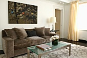 Sofa with grey velvet upholstery and glass table in classic living room