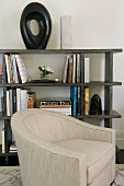 Pale armchair in front of half-height bookcase holding books and objet