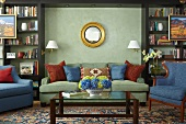 Antique armchair and modern sofa set against painted wall between black, wooden fitted shelves