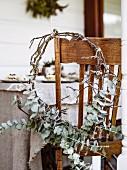Winterlicher Kranz aus Blätterzweigen an Stuhl auf Veranda