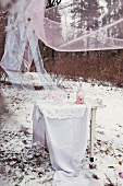 Home-made raspberry ice-cream on white table with floor-length table cloth below fluttering chiffon drapes