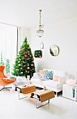 Christmas tree decorated with flowers in living room with white sofa and designer coffee table