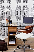 Desk and swivel chair in front of wallpapered wall