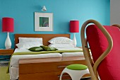 Colourful, fifties-style bedroom; double bed against turquoise wall and bedside lamps with red lampshades