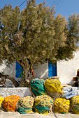 Colourful, rolled fishing nets and old tree in front of Mediterranean terrace of house with blue shutters