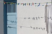 Colourful clothes pegs on washing line in front of exterior wall with pale blue wooden door