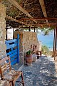Dicht bewachsene Pergola über Natursteinweg am Haus und Blick auf das Meer