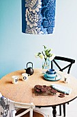 Revamped breakfast table with cork top, vintage chairs and pendant lamp with blue and white floral lampshade