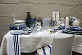 White and blue crockery and glasses on white tablecloth on table against roughly plastered wall