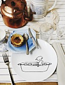 Place setting with comic-style line drawing on plate and ceramic saucer next to copper kettle