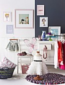 White child's dress on old tailor's dummy standing on round rug in front of chair and chest of drawers below framed pictures on wall painted half dark and half white